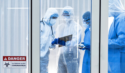 Healthcare workers in hazmat suits looking at a clipboard.