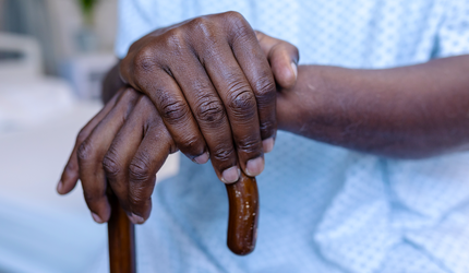 A Black man's hands resting on a cane.