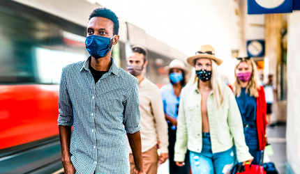 A group of masked travelers walking on a train platform.