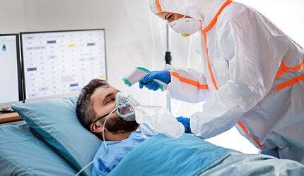 Man in hospital having temperature taken.