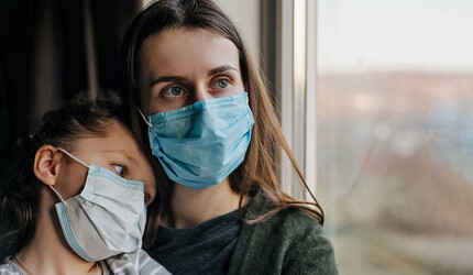 Mother and daughter wearing face mask looking out a window.