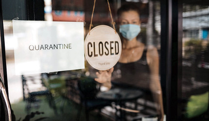 Shop owner in a surgical mask hanging a closed sign on the door of her business.