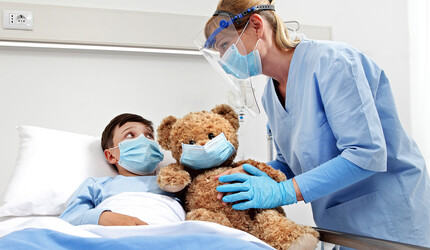 Child and health care worker in hospital room.