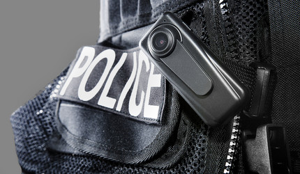 Image of a police vest with a body camera attached.