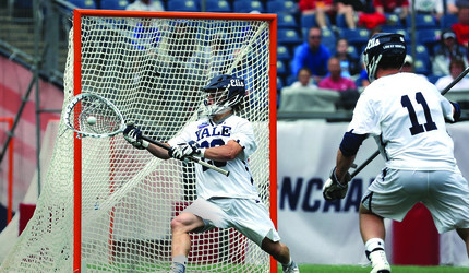 A Yale Lacrosse goalie catches a ball during play.
