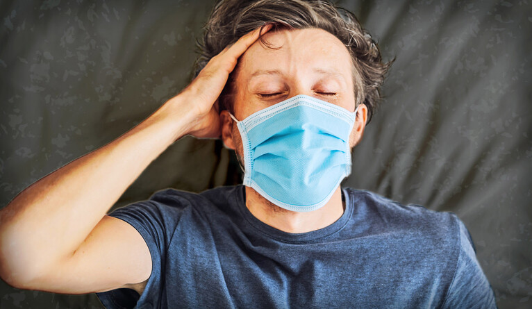 Man laying on bed wearing mask looking exhausted.