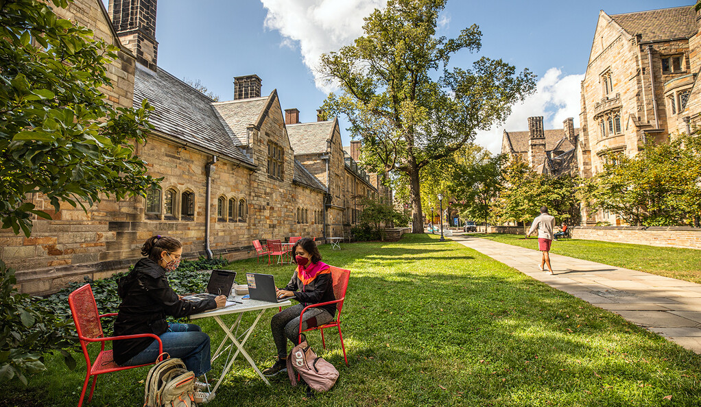 Two students sitting at a table in the shade.