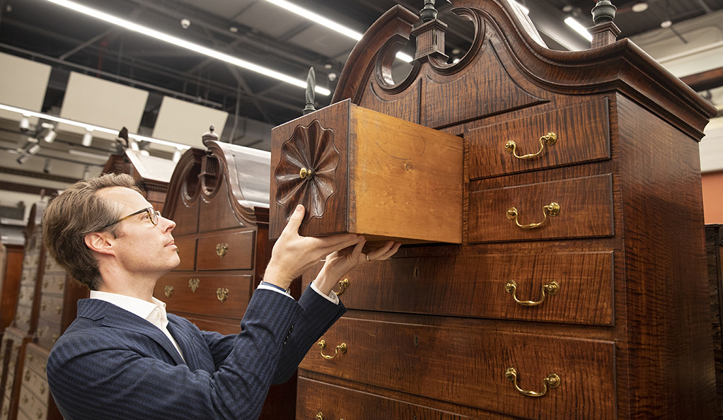 John Stuart Gordon places a drawer into an antique armoire at the new furniture study center.