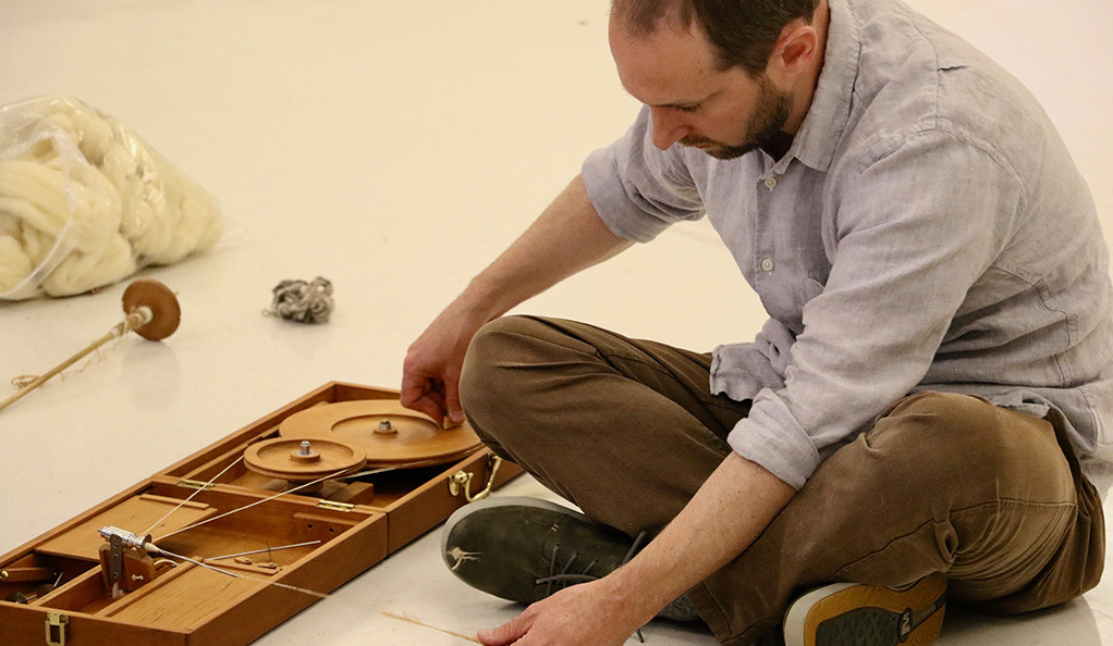 Fritz Horstman of The Joseph & Anni Albers Foundation experiments with a charkha, a portable, hand-cranked spinning wheel.