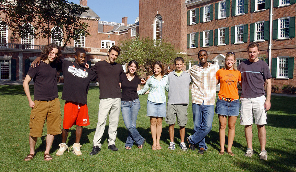 Students posing on a grassy dorm quad on the Yale University campus.