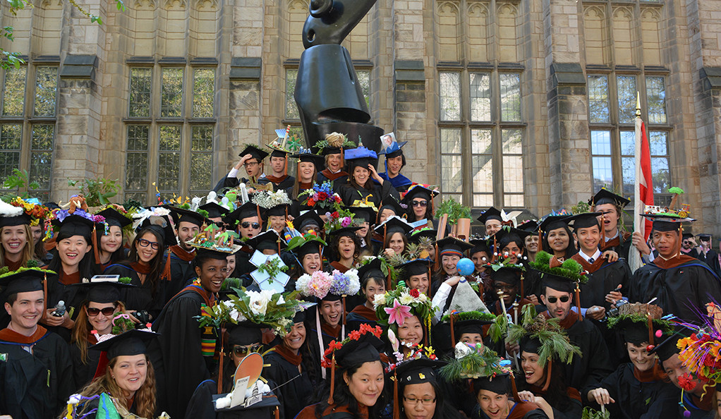 A group of Yale students gathering around a sculpture on campus in their graduation caps and gowns.