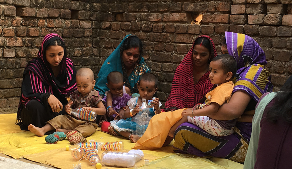 Mothers and children participate in a playgroup as part of an experiment in Odisha, India.