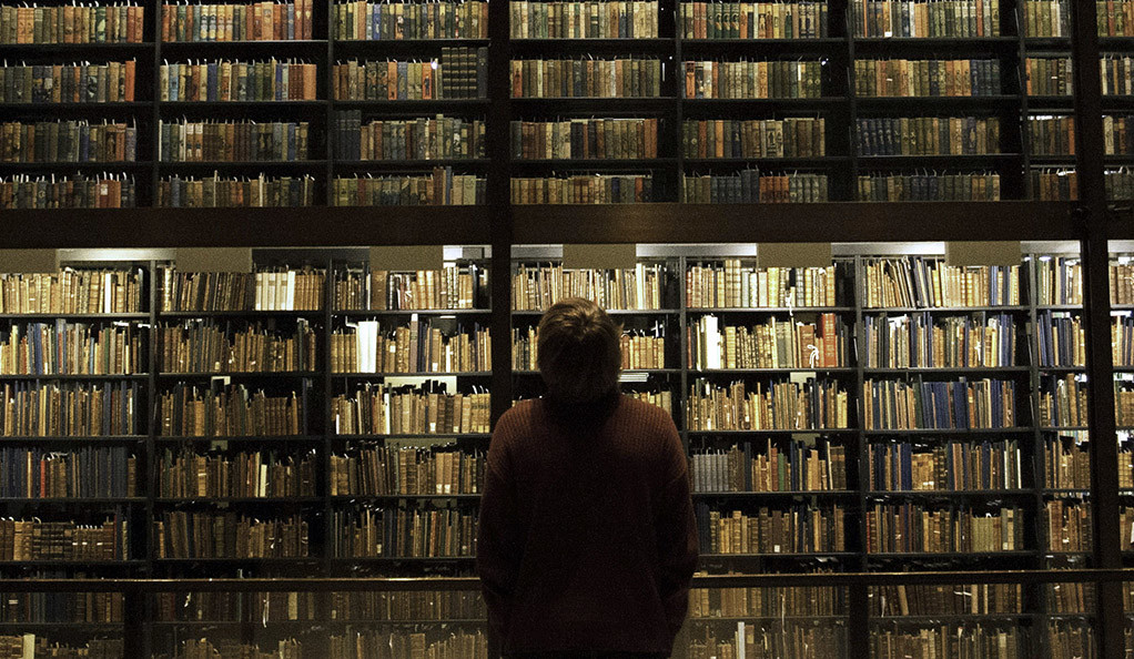 A person looking at bookshelves in Beinecke Library