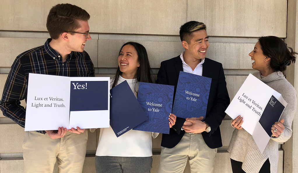 Yale admissions officers pose with welcome packets prepared for Decision Day.