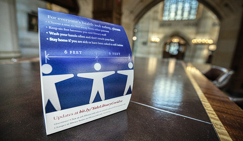A sign in Sterling Library asking patrons to stand six feet apart