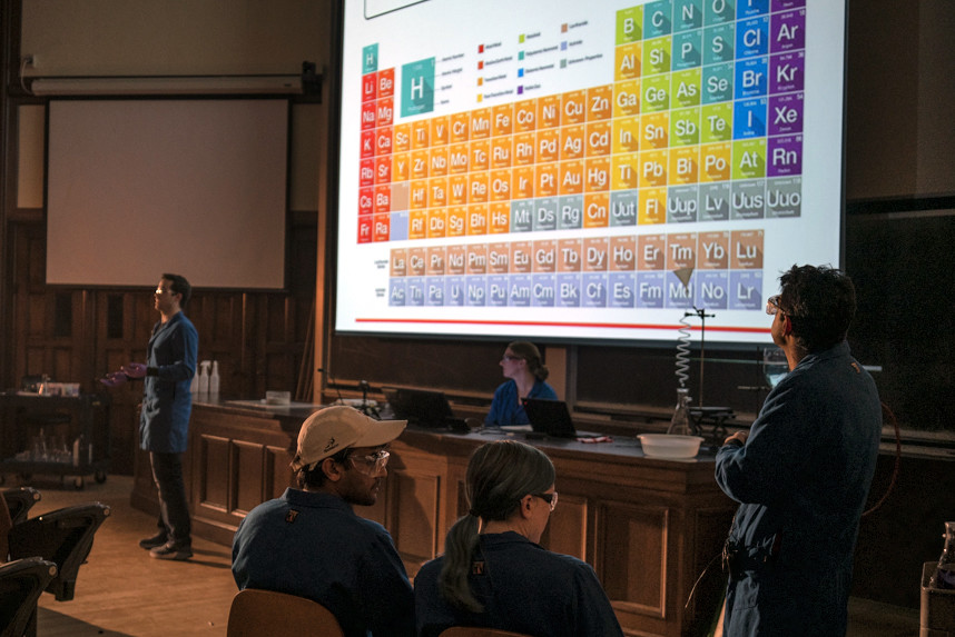 Students watch a presenter with a display of the periodic table of elements behind him
