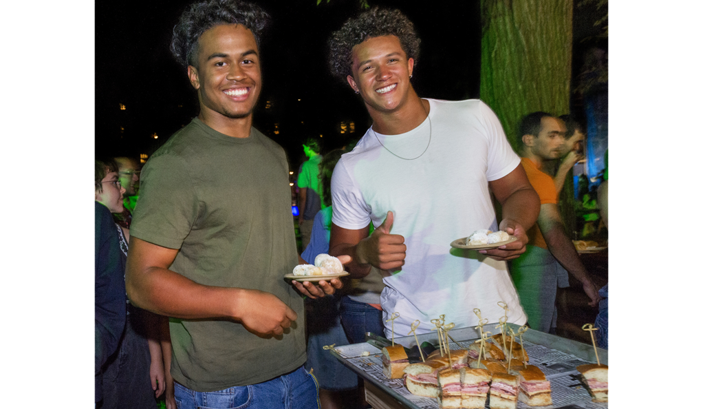 Two students eating muffallettas and beignets