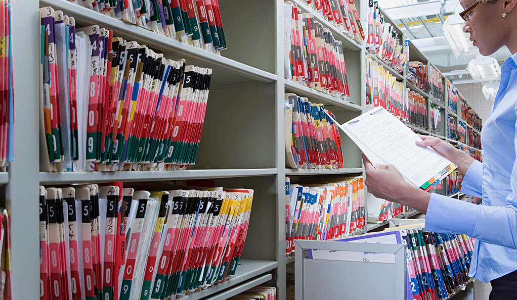 A woman pulling a file from a large shelf full of paper medical records.