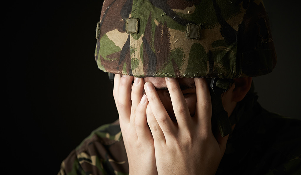A soldier in combat gear with his head in his hands.