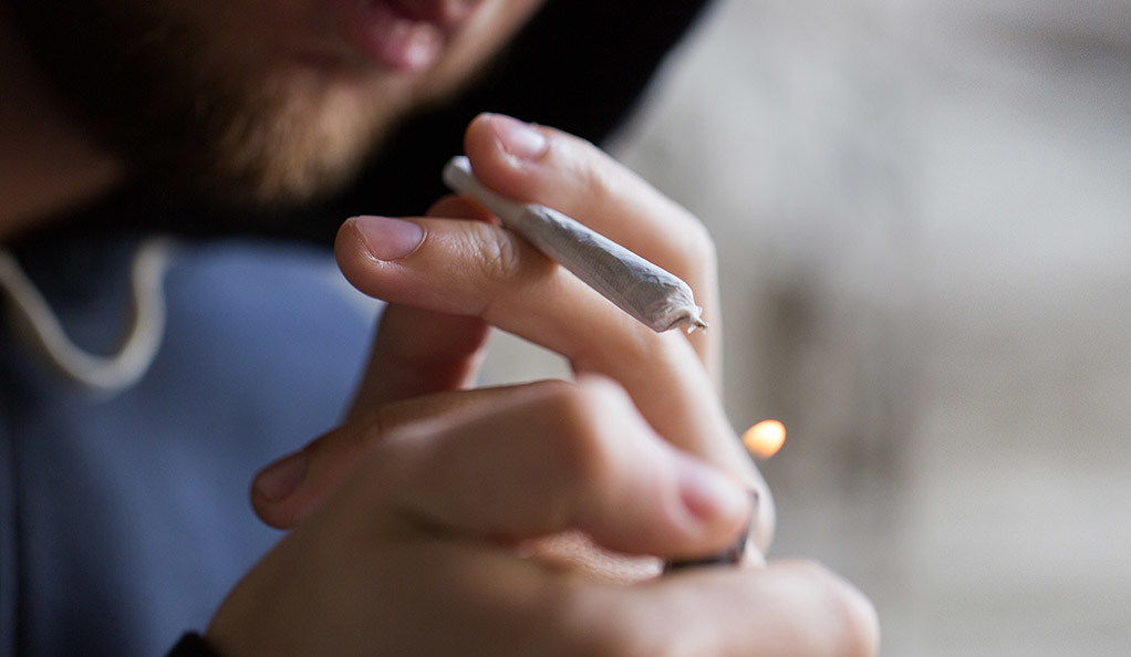 A man lighting a marijuana cigarette.
