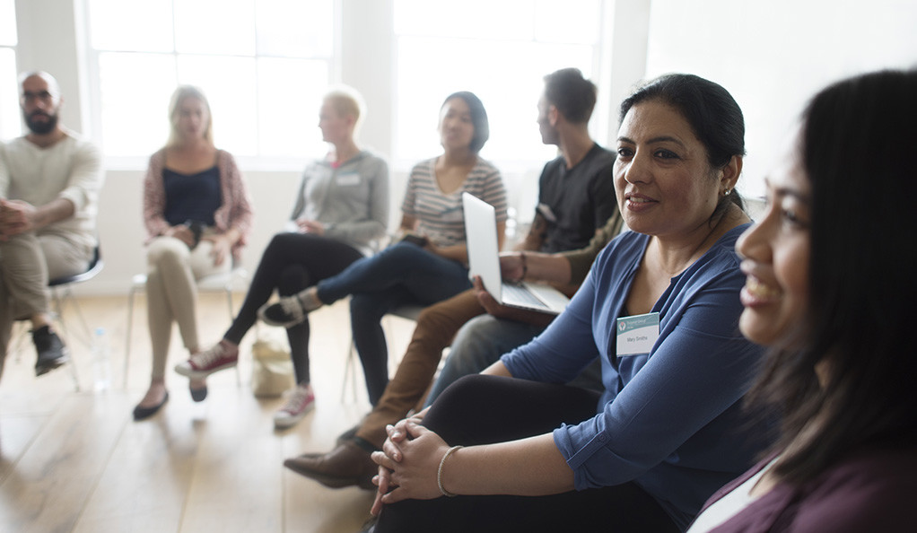 A woman speaking in a group therapy session.