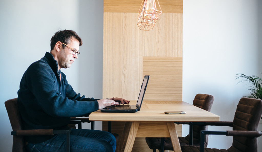 A man working at a laptop at a kitchen table.