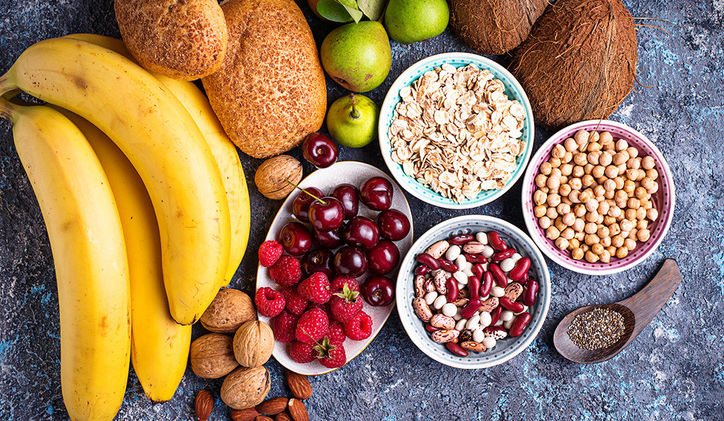 Healthy, high-fiber foods on a table: fruits, nuts, beans, and whole grains.