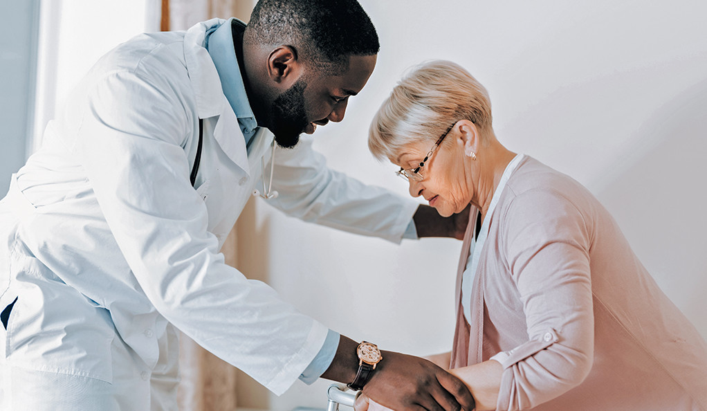 A doctor helping an elderly patient