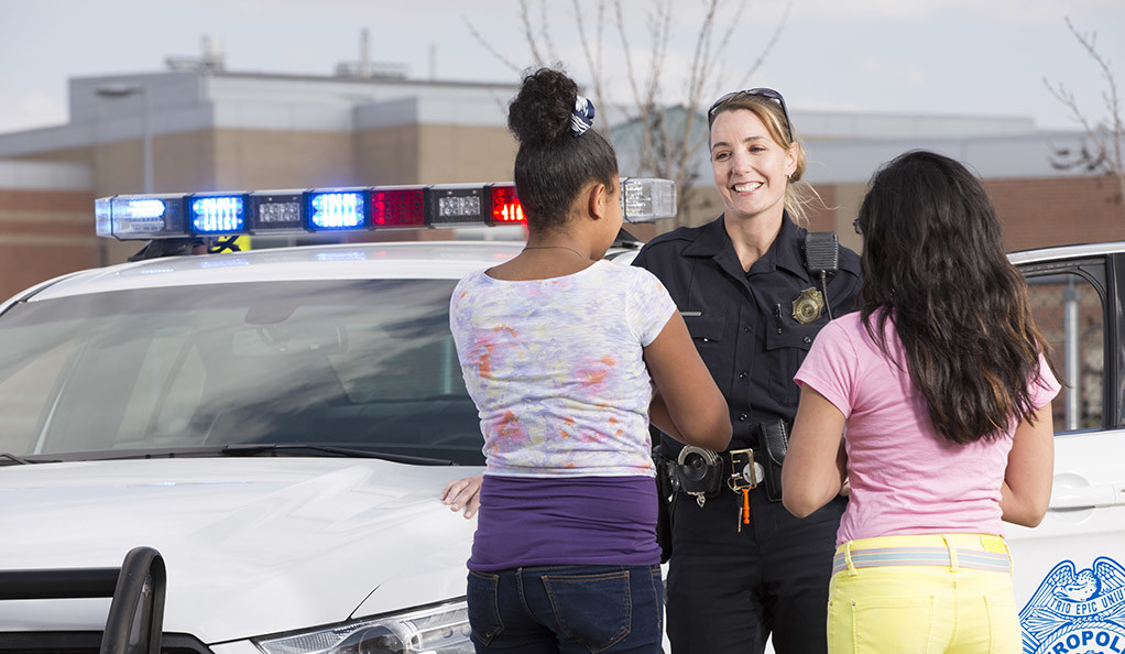 Police officer having a friendly conversation with two teen girls