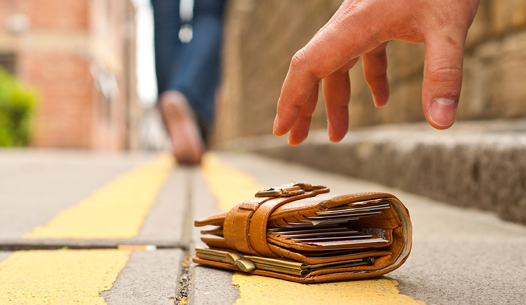 A man reaches to retrieve a lost wallet on the sidewalk. Will he return it?