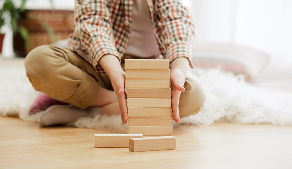 A young child very meticulously stacking blocks