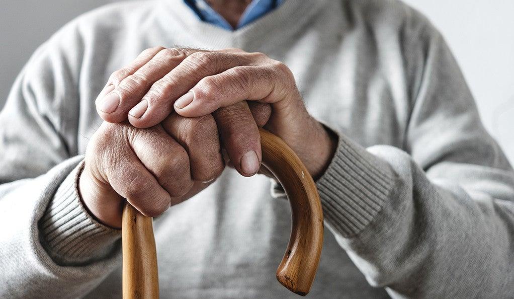 An elderly man with a cane