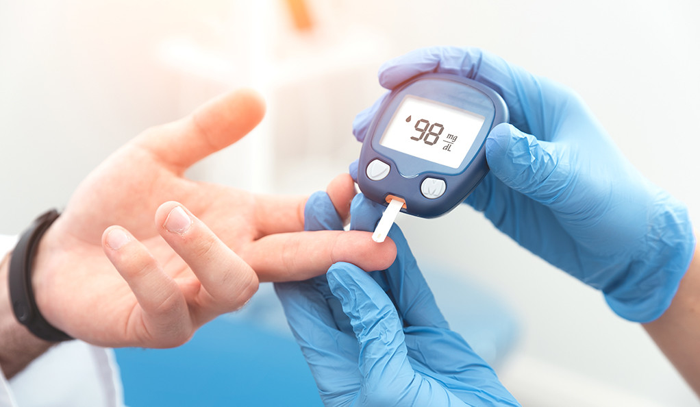 A doctor testing a patient's blood glucose level