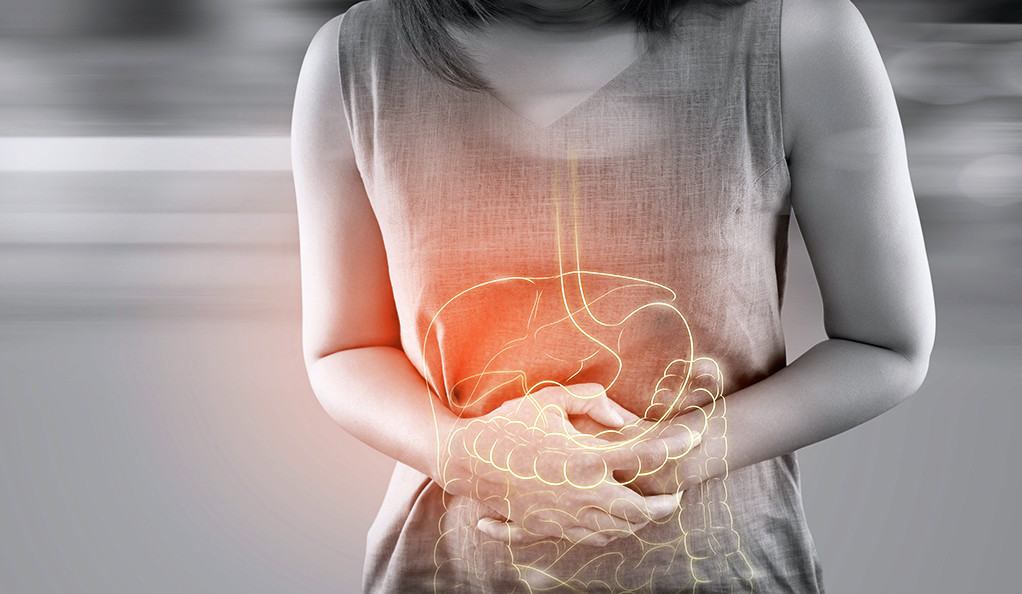 A woman clutching her stomach with an overlay of her large intestine.