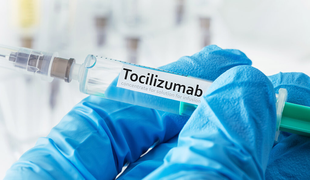 A doctor holding tocilizumab in a vial