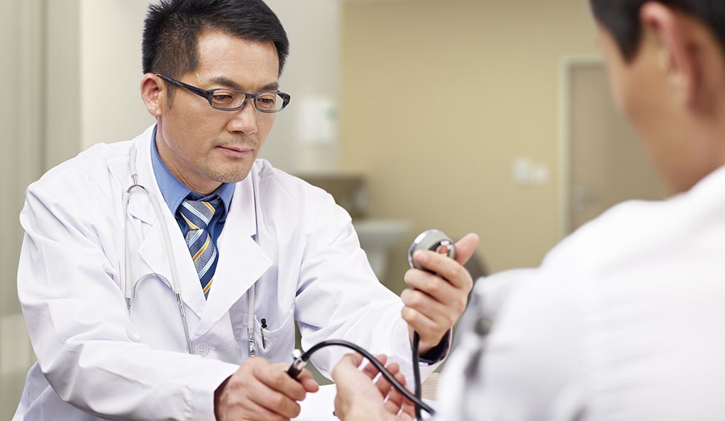 A Chinese doctor checking the blood pressure of a patient.