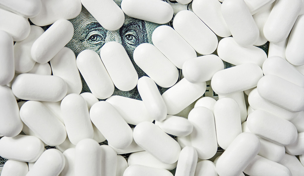 A pile of white pills with a hundred dollar bill visible underneath