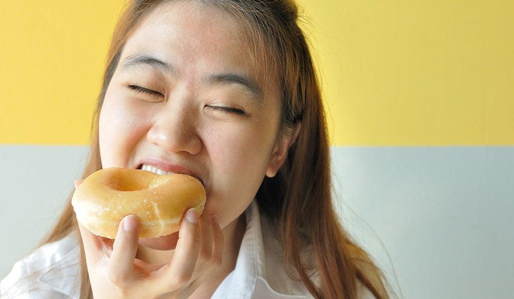 A woman biting into a glazed donut.