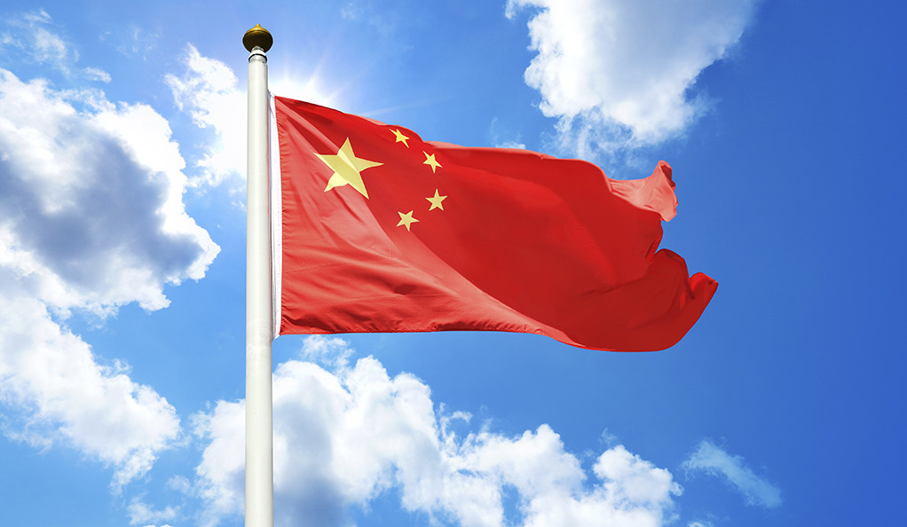 The Chinese flag against a sunny blue sky