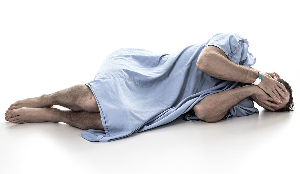 A man in a hospital gown on the ground with his face in his hands.