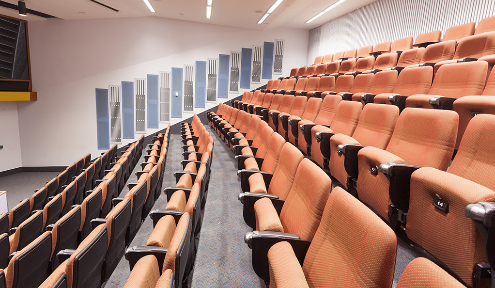 Rows of seats in an empty college lecture hall.