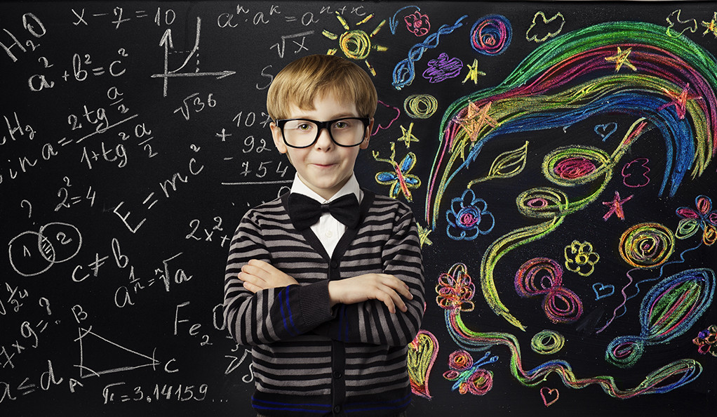 A young boy in glasses and a bow tie posing in front of mathematical equations and creative chalk art on a blackboard.