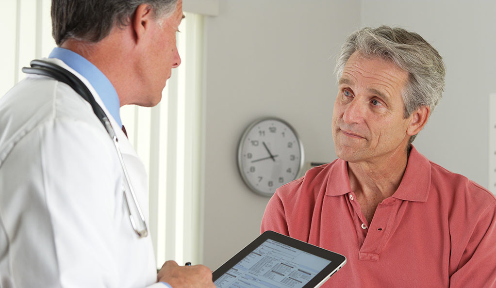 An elderly man talking to his doctor.