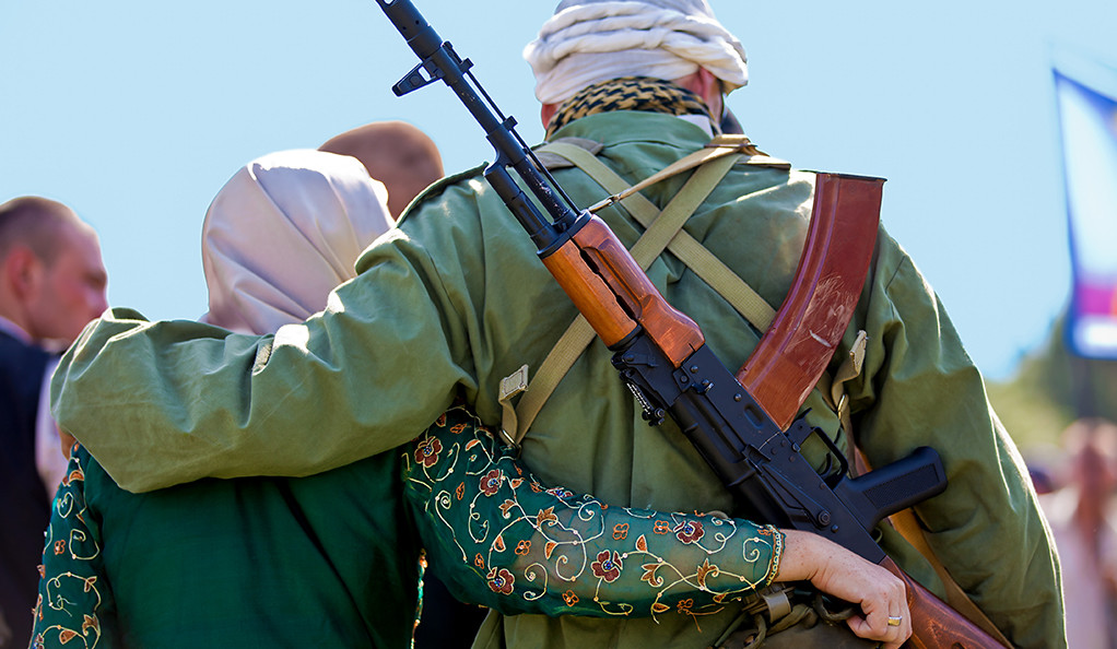 An Afghan woman and a man with a rifle on his back with their arms around each other.