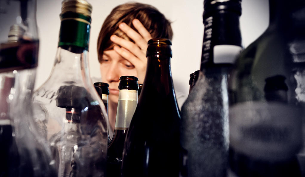 A person holding their head in their hand behind a table full of empty alcohol bottles.