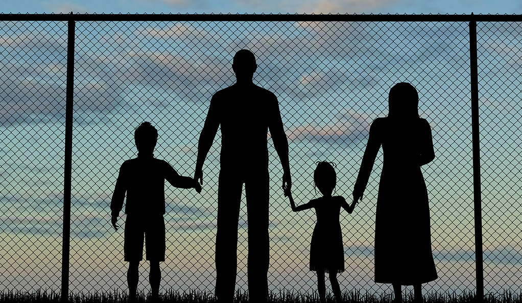 Silhouette of a refugees family with children, standing in front of chainlink fence at border