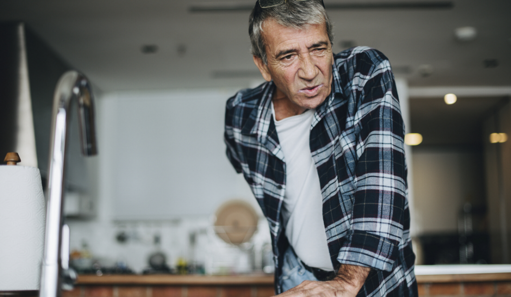 A senior man experiencing lower back pain