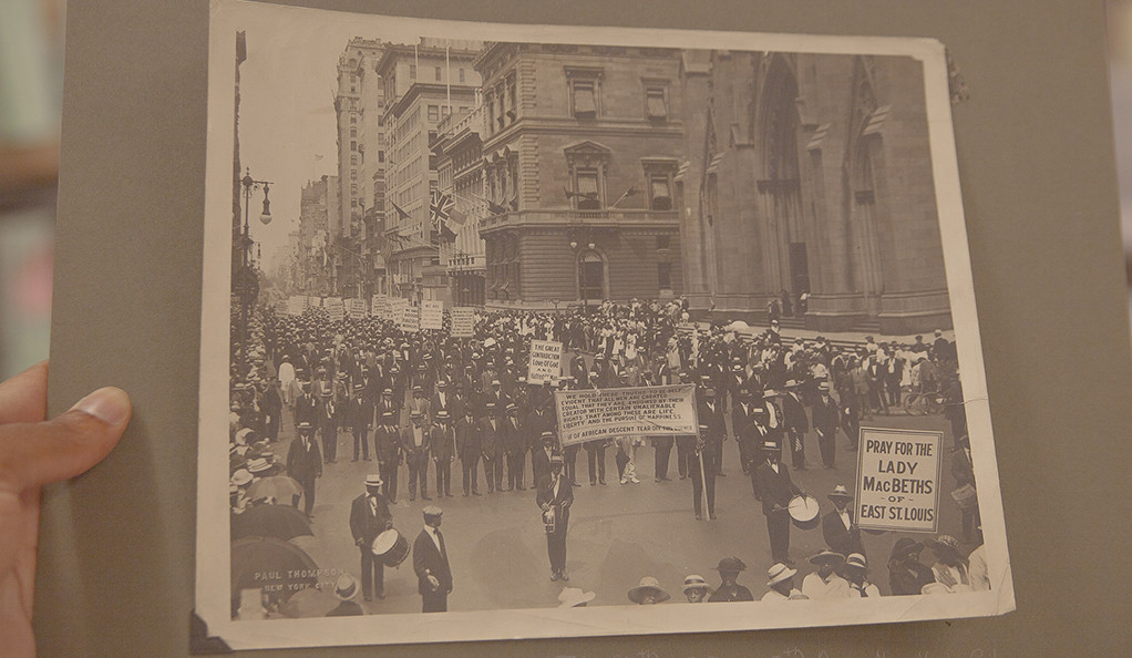 Image of hands holding an old black-and-white photo showing marchers holding signs.