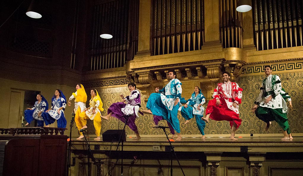 Students in colorful attire dance in Woolsey Hall.