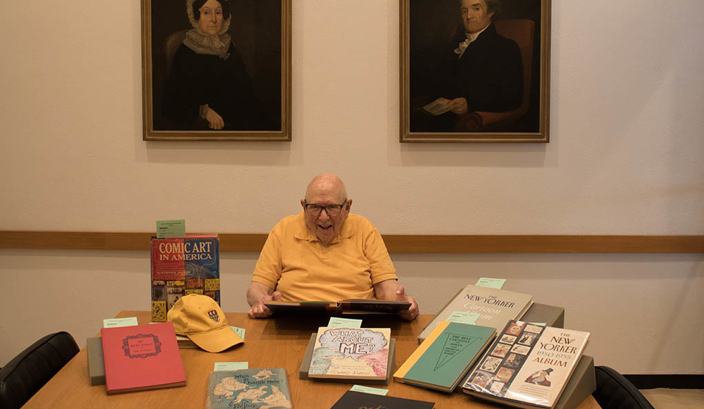 Bill Nightingale posing with some of his collection of cartoon books.